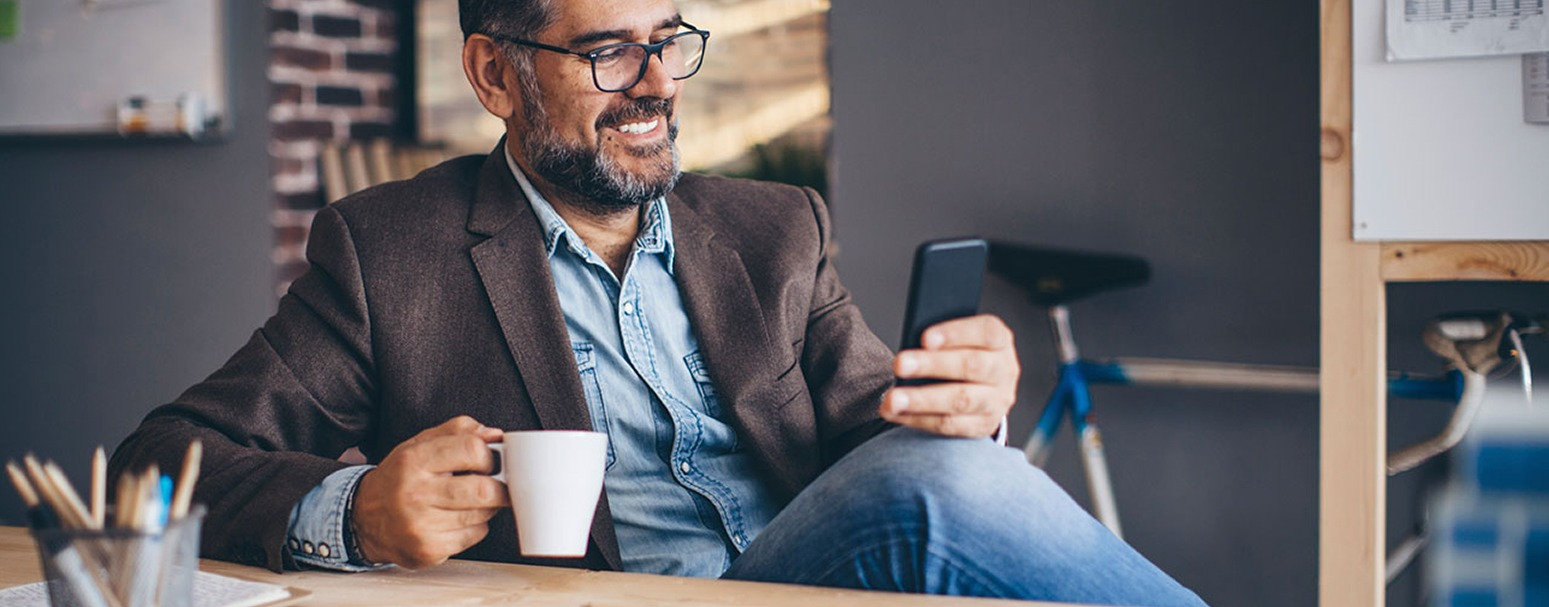Individual looking at his mobile device while drinking coffee
